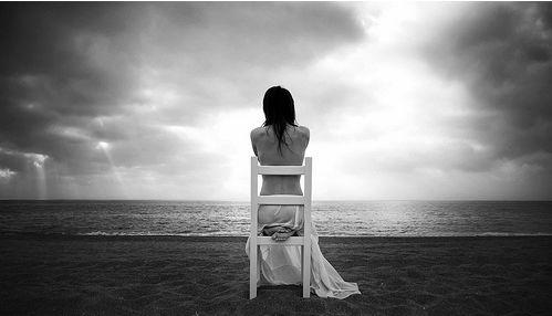chica sentada ante la playa